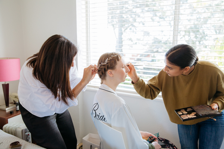 A wedding photo of a Bride having her hair and make up done. Photo taken by Auckland based wedding photographer Mala Photography.