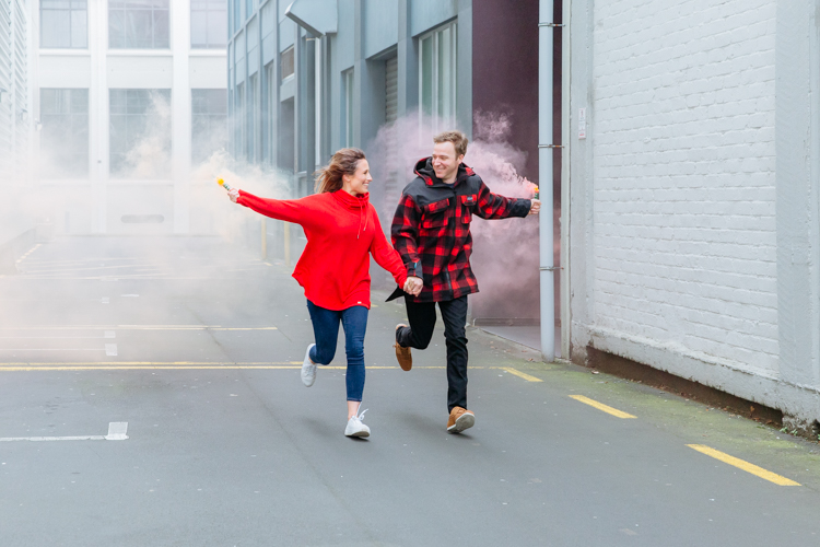 This is a photo of a newly engaged couple taken during their engagement shoot in Auckland. They are running through an alley way looking at each other smiling, holding hands and holding coloured smoke bombs as they run. They are dressed in bright red. This photo was taken by Mala Photography, an Auckland based wedding, engagement, portrait and event photographer.