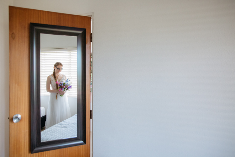 An artistic Bridal portrait taken by Mala Photography, a wedding photographer based in Auckland. The photo is of a Bride's reflection in a full length mirror hanging on the back of a bedroom door. The Bride is wearing a white wedding dress and looking down at the bridal bouquet she is holding.