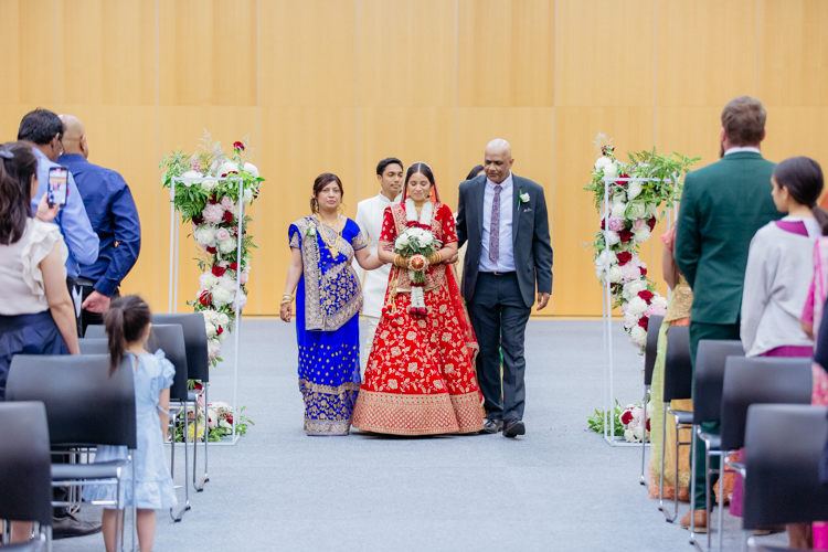 This is a photo of an Indian Bride entering her wedding with her uncle and auntie on either side of her. The Bride is wearing a traditional red wedding outfit. This photo was taken at the Lincoln Events Centre by Mala Photography, a wedding, portrait and event photographer that works New Zealand wide.