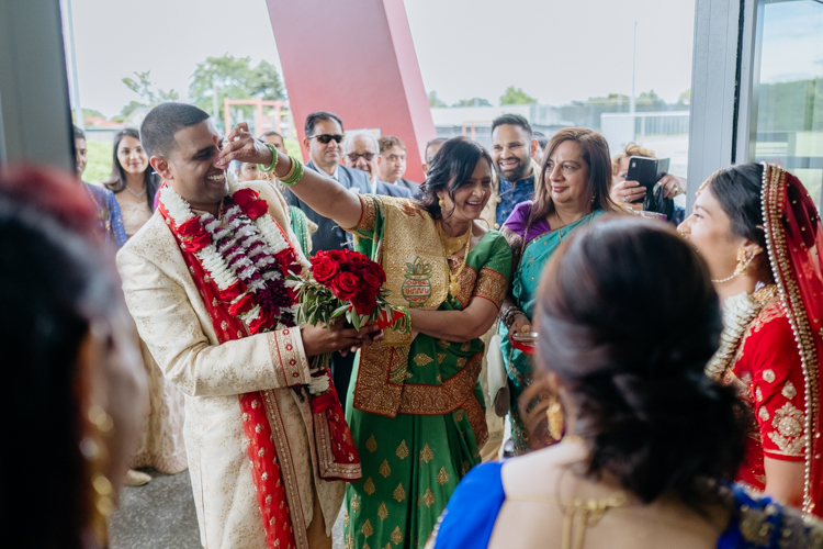 This is a photo taken by Mala Photography at a traditional Indian wedding. It's a photo of the Groom's entrance ceremony. It's conducted by a Hindu priest with the Groom and Bride's mother.