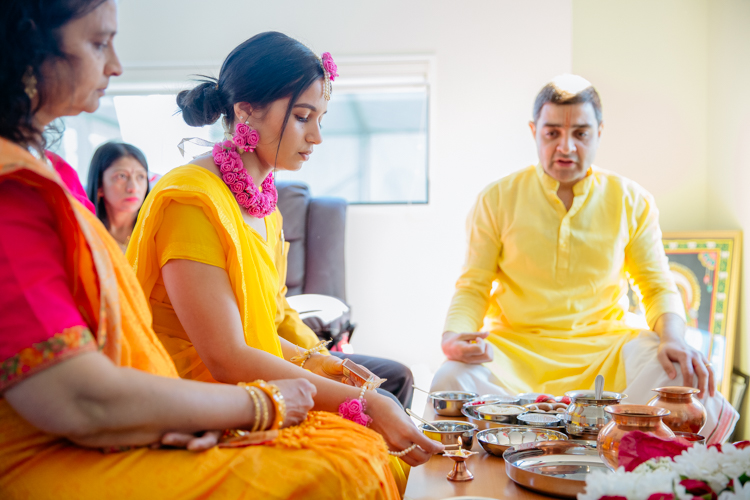 A photo of an Indian Bride dressed in a bright yellow sari performing pre-wedding Hindu rituals before her traditional Indian wedding. This photo was taken by Mala Photography, an Auckland based wedding, portrait and event photographer.