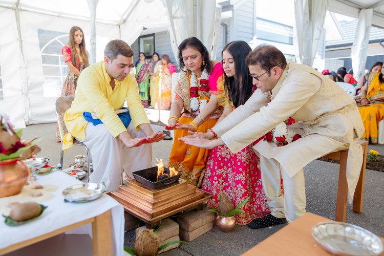 A photo of an Indian Bride and her parents dressed in a bright yellow sari performing pre-wedding Hindu rituals before her traditional Indian wedding. This photo was taken by Mala Photography, an Auckland based wedding, portrait and event photographer.