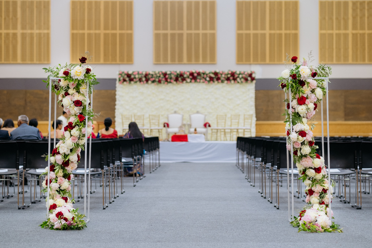 The large hall inside the Lincoln Events Centre styled and decorated with a mandap and aisle for a tradition Indian wedding. There are beautiful fresh flowers at the start of the aisle that have been arranged and sculpted into a column.