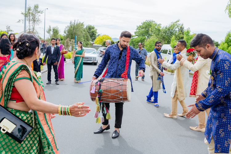 A groomsmen at a traditional Indian wedding at the Lincoln Events Centre in Christchurch dancing outside the venue before the wedding. A traditional Indian drummer is playing while the groomsmen and other guests dance.