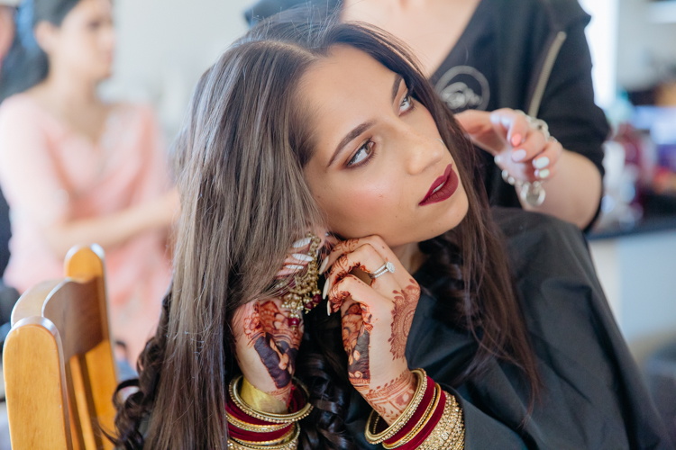 A photo of an Indian bride getting ready on her wedding day. She is having her done and putting in her earrings. Photo taken by Mala Photography, an Auckland wedding photographer that photographs Indian weddings.
