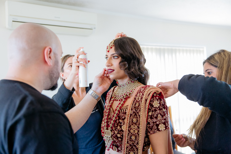 A photo of an Indian bride getting ready on her wedding day. She is having her hair and make up touched up. Photo taken by Mala Photography, an Auckland wedding photographer that photographs Indian weddings.