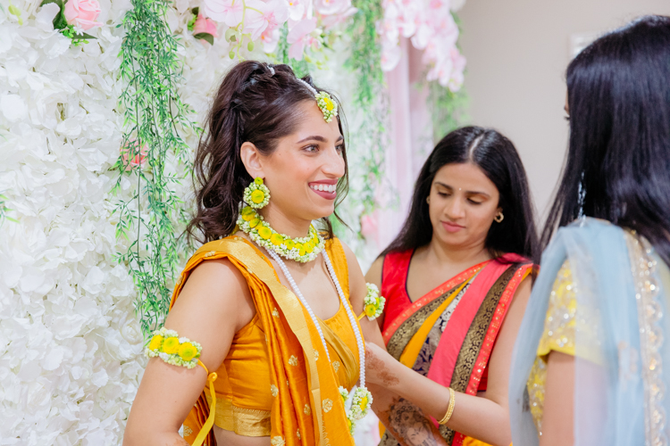 A photo of an Indian bride dressed in a bright yellow sari. This photo was taken on the day of her pre-wedding rituals, prayers and ceremonies. Photo taken by Mala Photography, an Auckland wedding photographer that specialises in Indian wedding photography.