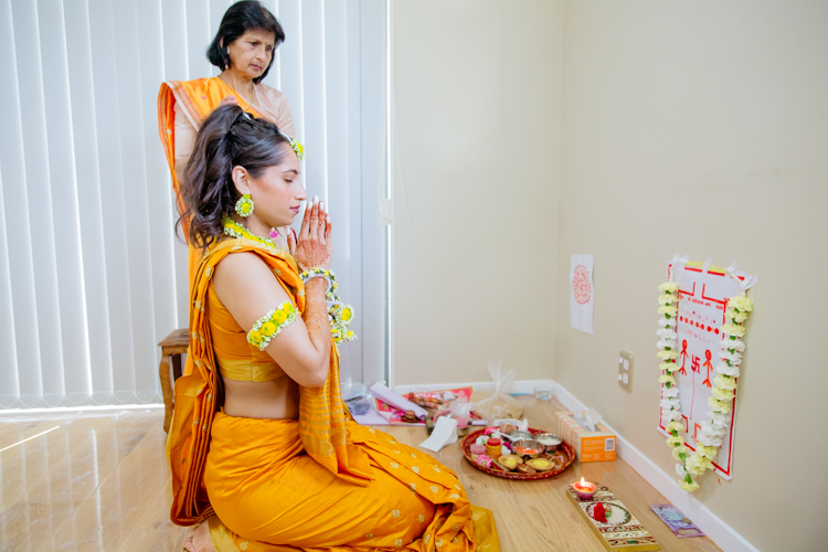 A photo of an Indian bride praying dressed in a bright yellow sari. This photo was taken on the day of her pre-wedding rituals, prayers and ceremonies. Photo taken by Mala Photography, an Auckland wedding photographer that specialises in Indian wedding photography.