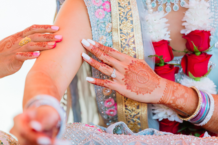 A close up photo of an Indian Bride's hand showing her bridal henna. This photo was taken on the day of her pre-wedding rituals, prayers and ceremonies. Photo was taken by Mala Photography, an Auckland based wedding photographer specialising in Indian weddings.