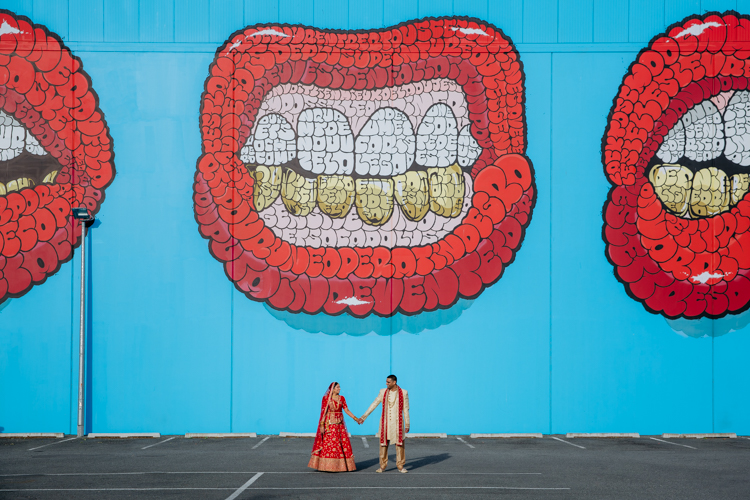 This is a photo from an Indian wedding in Christchurch, New Zealand. The photo is of a couple standing side by side holding hands in traditional Indian wedding outfits in front of a street art mural. The mural is of a bright red pair of lips on a bright blue background. Photo taken by Mala Photography, Auckland.