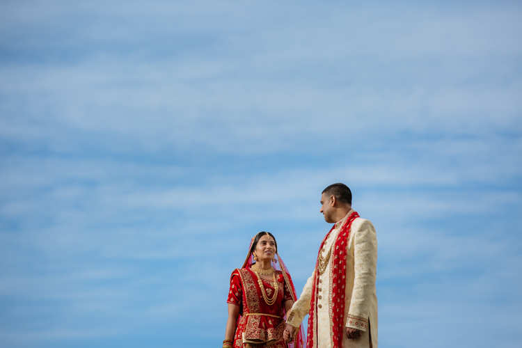 An Indian Bride and Groom standing on a earthquake ruin in Christchurch, New Zealand. They are wearing traditional Indian wedding attire and are standing side by side looking out in the same direction.