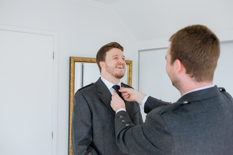 A groom wearing a kilt, shirt and tie getting ready on his wedding day. His groomsmen is helping him get ready and is adjusting his tie. Photo taken by a wedding photographer in Auckland, Mala Photography.
