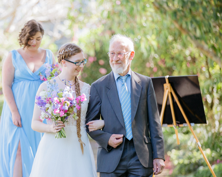 A Bride in a white wedding dress arriving at her wedding ceremony escorted by her father. They are both smiling. The Father of the Bride looks proud. Mala Photography, and Auckland based wedding photographer took this photo.