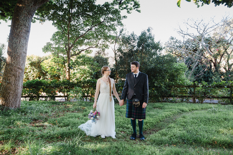 Photo of a Bride and Groom standing side by side in a garden holding hands. The Bride is in a white wedding dress and the Groom is wearing a kilt. Photo by Mala Photoraphy, a wedding photographer in Auckland.