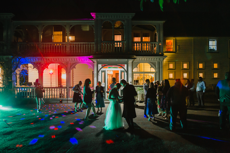 A wedding photo of a Bride and Groom taken during their first dance as husband and wife. They are dancing on an outdoor dancefloor at night. Photo by Mala Photography, an Auckland wedding photographer.